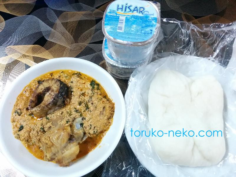 ナイジェリア料理の写真 画像 メロン ヤム芋からできたでんぷん質の食べ物、飲水が写っている